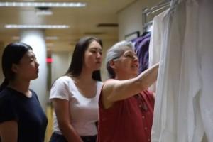 La costumière et deux assistantes nettoient et préparent les costumes.